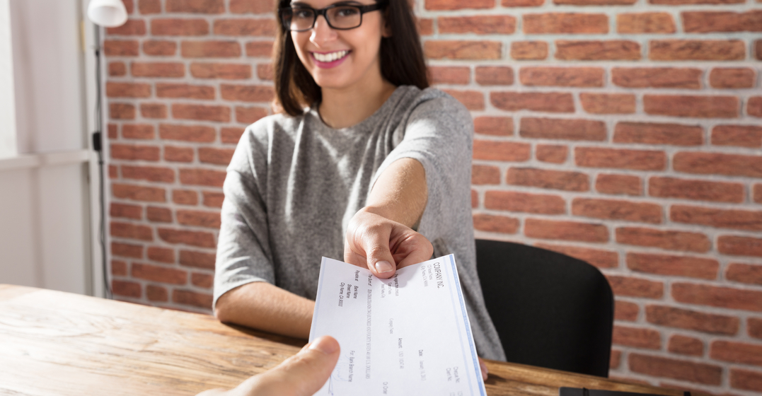 Woman sitting at a table smiling and handing over a cheque