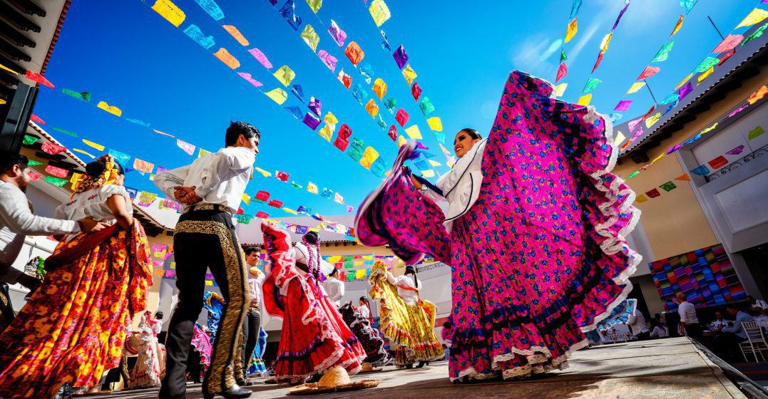 A man and a woman in traditional Mexican dresses dancing in a decorated street