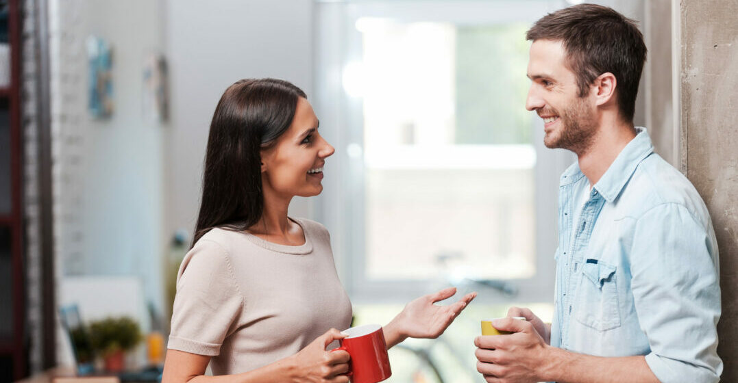 break. Two cheerful young people holding coffee cups and talking while standing in office