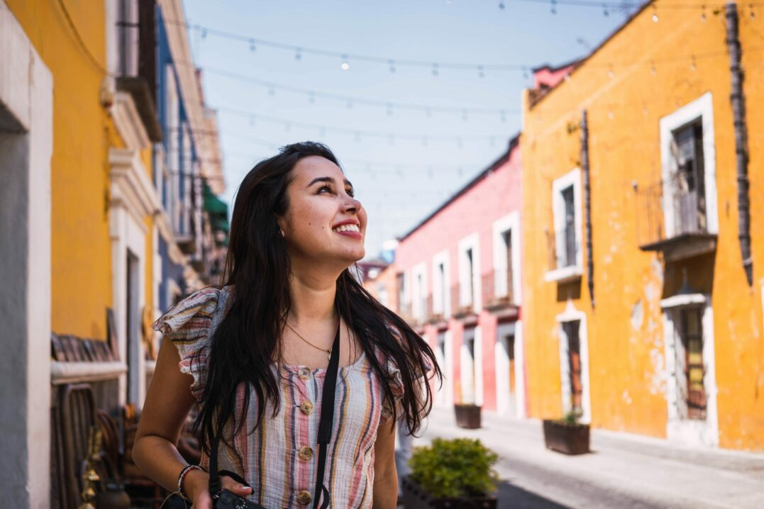 Smiling woman in a street with colorful houses