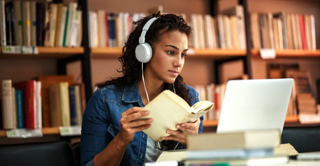 Young woman holding a book looking at a laptop