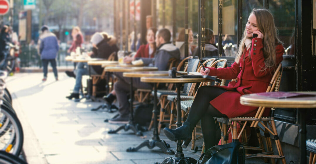 Moving to France- young woman sitting in a street café