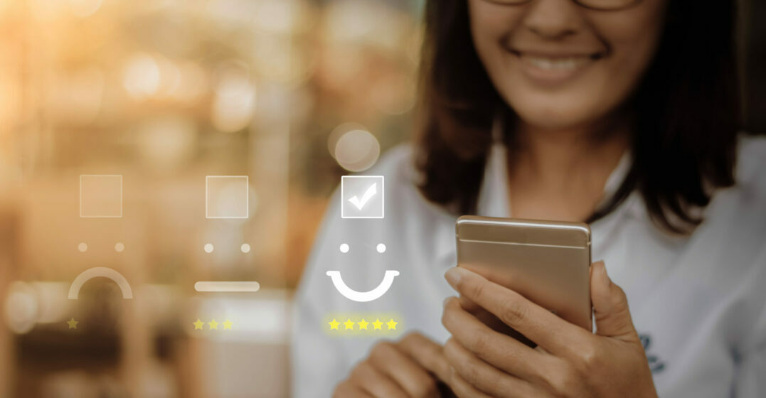 Smiling woman holding her smartphone, review icons in the background