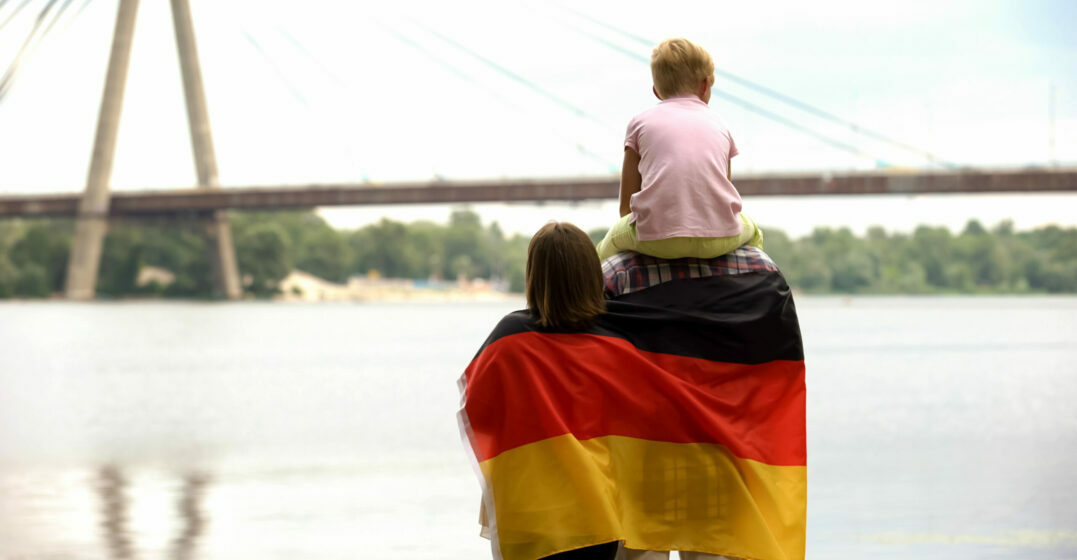 Family wrapped in German flag looking at bridge