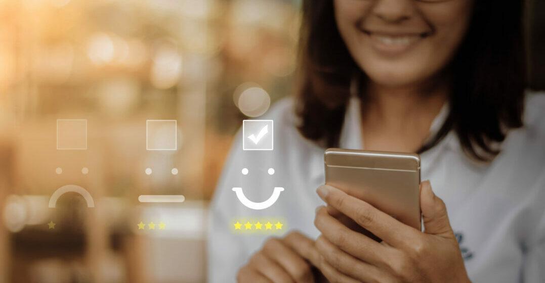 Lächelnde Frau am Smartphone, Bewertungs-Icons im Hintergrund