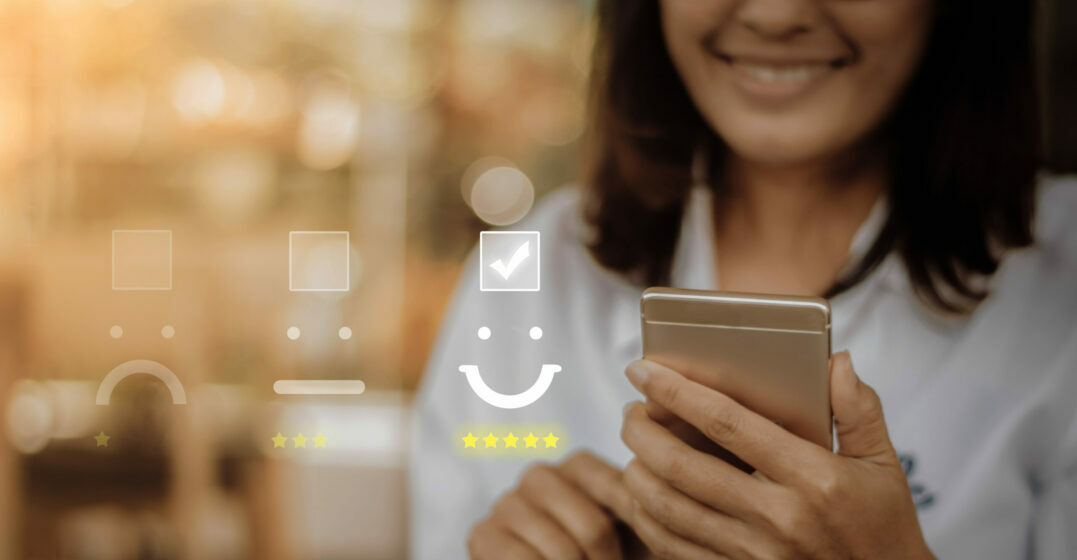 SMiling woman holding a phone, review icons in the background